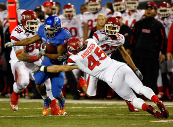 LAS VEGAS, NV - DECEMBER 22:  Doug Martin #22 of the Boise State Broncos is tackled by Boo Andersen #45 of the Utah Utes during the MAACO Bowl Las Vegas at Sam Boyd Stadium December 22, 2010 in Las Vegas, Nevada. Boise State won 26-3.  (Photo by Ethan Mil