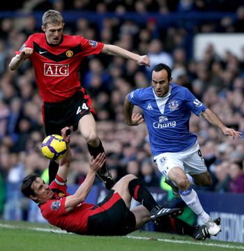 LIVERPOOL, ENGLAND - FEBRUARY 20:  Landon Donovan of Everton is challenged by Darren Fletcher and Gary Neville of Manchester United at Goodison Park on February 20, 2010 in Liverpool, England.  (Photo by Ross Kinnaird/Getty Images)