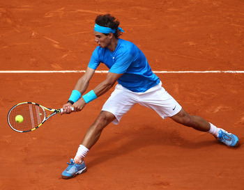 PARIS, FRANCE - MAY 30:  Rafael Nadal of Spain plays a backhand during the men's singles round four match between Rafael Nadal of Spain and Ivan Lubicic of Croatia on day nine of the French Open at Roland Garros on May 30, 2011 in Paris, France.  (Photo b