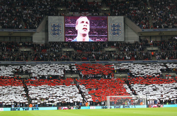 LONDON, ENGLAND - OCTOBER 12: Captain Rio Ferdinand of England is seen on the TV screen as England fans show their support during the national anthem during the UEFA EURO 2012 Group G Qualifying match between England and Montenegro at Wembley Stadium on O