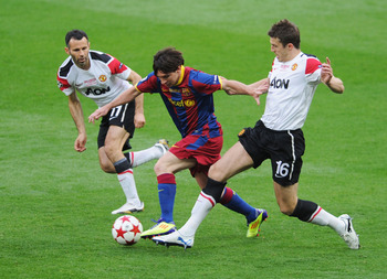 LONDON, ENGLAND - MAY 28:  Lionel Messi of FC Barcelona (C) is challenged by Ryan Giggs (L) and Michael Carrick of Manchester United during the UEFA Champions League final between FC Barcelona and Manchester United FC at Wembley Stadium on May 28, 2011 in