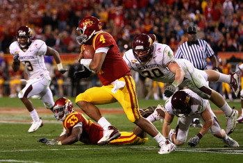 TEMPE, AZ - DECEMBER 31:  Quarterback Austen Arnaud #4 of the Iowa State Cyclones scrambles with the ball past Lee Campbell #30 of the Minnesota Golden Gophers during the Insight Bowl at Arizona Stadium on December 31, 2009 in Tempe, Arizona. The Cyclones