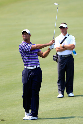 PONTE VEDRA BEACH, FL - MAY 10:  Tiger Woods (L) hits a shot as his instructor Sean Foley (R) looks on during a practice round prior to the start of THE PLAYERS Championship held at THE PLAYERS Stadium course at TPC Sawgrass on May 10, 2011 in Ponte Vedra