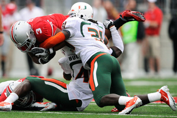 COLUMBUS, OH - SEPTEMBER 11:  Ramon Buchanan #45 of the Miami Hurricanes and Sean Spence #31 of the Hurricanes bring down Brandon Saine #3 of the Ohio State Buckeyes at Ohio Stadium on September 11, 2010 in Columbus, Ohio.  (Photo by Jamie Sabau/Getty Ima