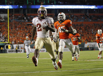 MIAMI, FL - OCTOBER 9: Lonnie Pryor #24 of the Florida State Seminoles scores a touchdown while being pursued by Ramon Buchanan #45 of the Miami Hurricanes on October 9, 2010 at Sun Life Stadium in Miami, Florida. The Seminoles defeated the Hurricanes 45-