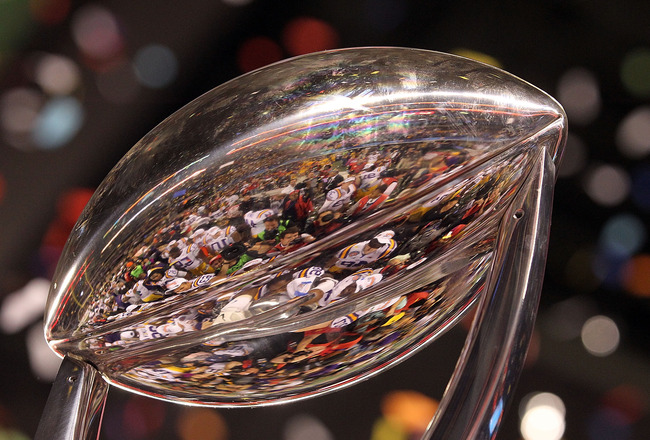 ARLINGTON, TX - JANUARY 07:  The LSU Tigers are reflected in the Cotton Bowl Championship trophy while celebrating a 41-24 win against the Texas A&M Aggies during the AT&T Cotton Bowl at Cowboys Stadium on January 7, 2011 in Arlington, Texas.  (Photo by R