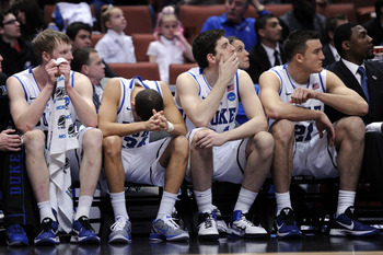 ANAHEIM, CA - MARCH 24:  Kyle Singler #12, Seth Curry #30, Ryan Kelly #34 and Miles Plumlee #21 of the Duke Blue Devils look on from the bench against the Arizona Wildcats during the west regional semifinal of the 2011 NCAA men's basketball tournament at