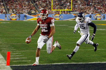 GLENDALE, AZ - JANUARY 01:  Tight end James Hanna #82 of the Oklahoma Sooners catches a touchdown pass in the first quarter past Jerome Junior #15 of the Connecticut Huskies during the Tostitos Fiesta Bowl at the Universtity of Phoenix Stadium on January