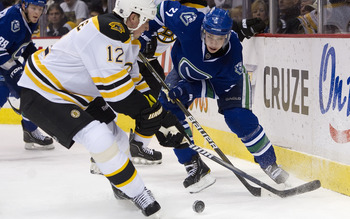 VANCOUVER, CANADA - FEBRUARY 26: Mason Raymond #21 of the Vancouver Canucks tries to chip the puck past Tomas Kaberle #12 of the Boston Bruins during the second period in NHL action on February 26, 2011 at Rogers Arena in Vancouver, British Columbia, Cana