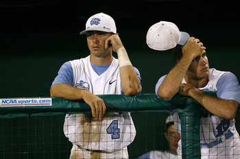 OMAHA, NE - JUNE 24:  Garrett Gore #4 and Rob Catapano #15 of the North Carolina Tar Heels stand dejected as the Oregon State Beavers celebrate their 9-3 win in Game 2 to claim their second straight NCAA College World Series Championship at Rosenblatt Sta