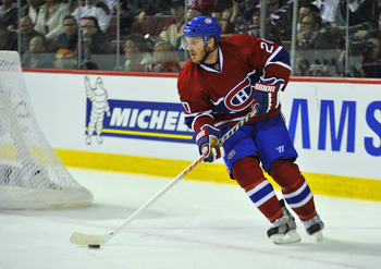 MONTREAL, CANADA - APRIL 18:  James Wisniewski #20 of the Montreal Canadiens turns up ice with the puck in Game Three of the Eastern Conference Quarterfinals against the Boston Bruins during the 2011 NHL Stanley Cup Playoffs at the Bell Centre on April 18