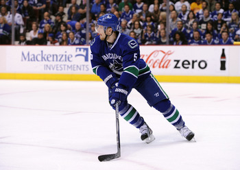 VANCOUVER, CANADA - MAY 15:  Christian Ehrhoff #5 of the Vancouver Canucks looks to pass the puck out of the defensive zone against the San Jose Sharks in the first period in Game One of the Western Conference Finals during the 2011 Stanley Cup Playoffs a