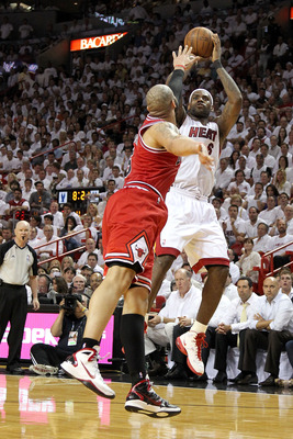 MIAMI, FL - MAY 24:  LeBron James #6 of the Miami Heat attempts a shot as Carlos Boozer #5 of the Chicago Bulls puts his hand over his face in Game Four of the Eastern Conference Finals during the 2011 NBA Playoffs on May 24, 2011 at American Airlines Are