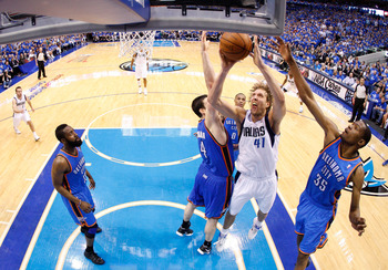 DALLAS, TX - MAY 25:  Dirk Nowitzki #41 of the Dallas Mavericks goes up for a shot between Nick Collison #4 and Kevin Durant #35 of the Oklahoma City Thunder in the second half in Game Five of the Western Conference Finals during the 2011 NBA Playoffs at