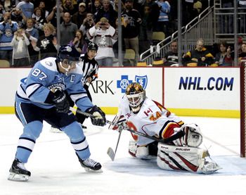 PITTSBURGH - NOVEMBER 27:  Miikka Kiprusoff #34 of the Calgary Flames makes a glove save on Sidney Crosby #87 of the Pittsburgh Penguins on a penalty shot at Consol Energy Center on November 27, 2010 in Pittsburgh, Pennsylvania.  (Photo by Justin K. Aller