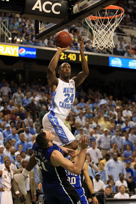 GREENSBORO, NC - MARCH 13:  Justin Watts #24 of the North Carolina Tar Heels shoots against Miles Plumlee #21 of the Duke Blue Devils during the second half in the championship game of the 2011 ACC men's basketball tournament at the Greensboro Coliseum on