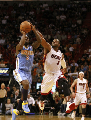 MIAMI, FL - MARCH 19:  Guard Dwyane Wade #3 of the Miami Heat blocks the shot of guard Ty Lawson #3 (R) of the Denver Nuggets at American Airlines Arena on March 19, 2011 in Miami, Florida. NOTE TO USER: User expressly acknowledges and agrees that, by dow