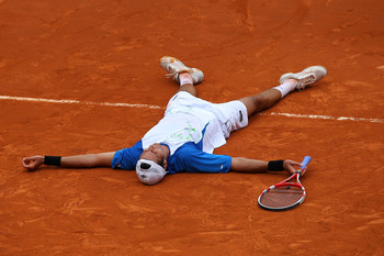 PARIS, FRANCE - MAY 30:  Juan Ignacio Chela of Argentina falls to the court as he celebrates matchpoint during the men's singles round four match between Alejandro Falla of Columbia and Juan Ignacio Chela of Argentina on day nine of the French Open at Rol