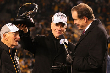 PITTSBURGH, PA - JANUARY 23:  Owner Dan Rooney (L) and Team president Art Rooney II (2ndL) of the Pittsburgh Steelers recieve the Lamar Hunt Trophy as CBS sportscaster Jim Nantz looks on after their 24 to 19 win over the New York Jets in the 2011 AFC Cham