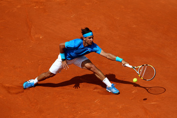 PARIS, FRANCE - MAY 28:  Rafael Nadal of Spain stretches to hit a forehand during the men's singles round three match between Rafael Nadal of Spain and Antonio Veic of Croatia on day seven of the French Open at Roland Garros on May 28, 2011 in Paris, Fran