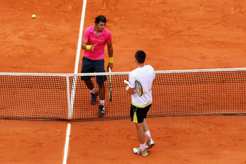 PARIS - MAY 31:  Robin Soderling (below net) of Sweden goes to shake hands with Rafael Nadal of Spain following his victory during the Men's Singles Fourth Round  match on day eight of the French Open at Roland Garros on May 31, 2009 in Paris, France.  (P