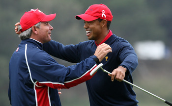 SAN FRANCISCO - OCTOBER 11:  Fred Couples the Captain of the USA Team races to congratulate Tiger Woods after he had holed the winning putt at the 13th hole where he beat his opponent Y.E.Yang 6&5 during the Day Four Singles Matches in The Presidents Cup
