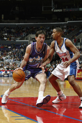 LOS ANGELES - NOVEMBER 26:  John Stockton #12 of the Utah Jazz drives against Andre Miller #24 of the Los Angeles Clippers during the game at Staples Center on November 26, 2002 in Los Angeles, California.  The Jazz won 99-94.  NOTE TO USER: User expressl