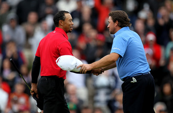 THOUSAND OAKS, CA - DECEMBER 05:  Graeme McDowell of Northern Ireland (R) and Tiger Woods shake hands on the 18th green after they finished regulation in a tie during the final round of the Chevron World Challenge at Sherwood Country Club on December 5, 2