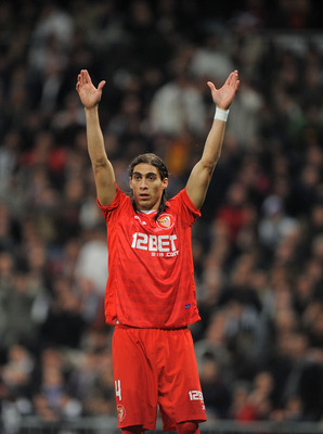 MADRID, SPAIN - FEBRUARY 02: Martin Caceres of Sevilla signals to a teammate during the Copa del Rey semi-final second leg match between Real Madrid and Sevilla at Estadio Santiago Bernabeu on February 2, 2011 in Madrid, Spain.  (Photo by Denis Doyle/Gett