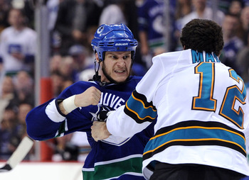 VANCOUVER, BC - MAY 18:  Kevin Bieksa #3 of the Vancouver Canucks prepares to throw a punch at Patrick Marleau #12 of the San Jose Sharks in the second period in Game Two of the Western Conference Finals during the 2011 Stanley Cup Playoffs at Rogers Aren