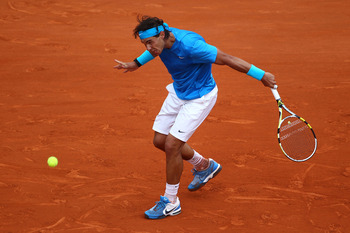 PARIS, FRANCE - MAY 30:  Rafael Nadal of Spain hits a backhand during the men's singles round four match between Rafael Nadal of Spain and Ivan Lubicic of Croatia on day nine of the French Open at Roland Garros on May 30, 2011 in Paris, France.  (Photo by