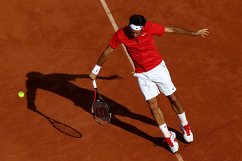 PARIS, FRANCE - MAY 31:  Roger Federer of Switzerland hits a backhand during the men's singles quarterfinal match between Gael Monfils of France and Roger Federer of Switzerland on day ten of the French Open at Roland Garros on May 31, 2011 in Paris, Fran