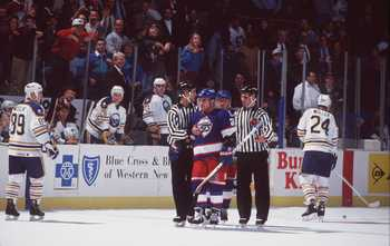 19 Nov 1993: DEFENSEMAN TIE DOMI #20 OF THE WINNIPEG JETS IS ESCORTED BY OFFICIALS PAST FORWARD ALEXANDER MOGILNY OF THE BUFFALO SABRES DURING A JETS GAME AGAINST THE SABRES AT THE AUD IN BUFFALO, NEW YORK.