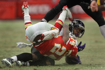 KANSAS CITY, MO - JANUARY 09:  Cornerback Brandon Flowers #24 of the Kansas City Chiefs rolls over running back Ray Rice #27 of the Baltimore Ravens after making the tackle during the 2011 AFC wild card playoff game at Arrowhead Stadium on January 9, 2011