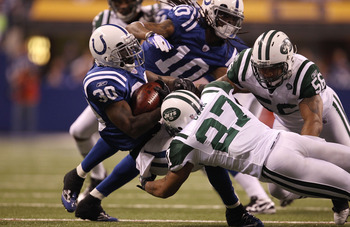INDIANAPOLIS, IN - JANUARY 08:  Dominic Rhodes #30 of the Indianapolis Colts is tackled by Emanuel Cook #27 of the New York Jets during their 2011 AFC wild card playoff game at Lucas Oil Stadium on January 8, 2011 in Indianapolis, Indiana. The Jets won 17