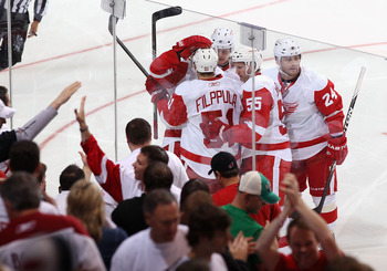 The Detroit Red Wings celebrate a goal as fans cheer the boys along.