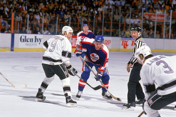 INGLEWOOD, CA - 1988:  Bernie Nicholls #9 of the Los Angeles Kings lines up for the face-off against Thomas Steen #25 of the Winnipeg Jets during their game at the Great Western Forum circa 1988 in Inglewood, California.  (Photo by Mike Powell/Getty Image