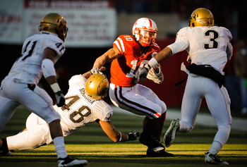 LINCOLN, NE - NOVEMBER 26: Roy Helu Jr. #10 of the Nebraska Cornhuskers slips past Liloa Nobriga #48 of the Colorado Buffaloes during their game at Memorial Stadium on November 26, 2010 in Lincoln, Nebraska. Nebraska defeated Colorado 45-17 (Photo by Eric