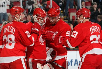 DETROIT - FEBRUARY 12:  Brian Rafalski #28, Valtteri Filppula #51 and Kris Draper #33 of the Detroit Red Wings congratulates goaltender Chris Osgood #30 after their NHL game against the Minnesota Wild at Joe Louis Arena on February 12, 2009 in Detroit, Mi