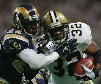 ST. LOUIS - SEPTEMBER 26:  Ki-Jana Carter #32 of the New Orleans Saints tries to break the tackle of Jeramitrius Butler #23 of the St. Louis Rams during the third quarter at the Edward Jones Dome on September 26, 2004 in St. Louis, Missouri.  The Saints w