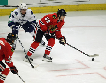 CHICAGO, IL - APRIL 24: Patrick Kane #88 of the Chicago Blackhawks shoots the puck in front of Alexandre Burrows #14 of the Vancouver Canucks in Game Six of the Western Conference Quarterfinals during the 2011 NHL Stanley Cup Playoffs at the United Center