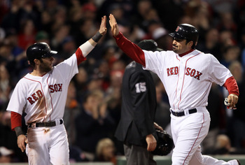 BOSTON, MA - MAY 22:  Dustin Pedroia #15 and Adrian Gonzalez #28 of the Boston Red Sox celebrate after they scored in the seventh inning against the Chicago Cubs on May 22, 2011 at Fenway Park in Boston, Massachusetts.  Before this series, the two teams h