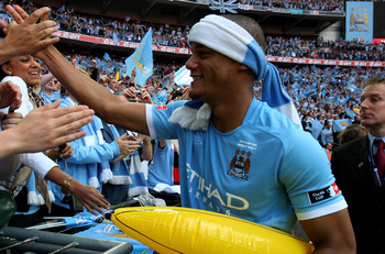 LONDON, ENGLAND - MAY 14:   Vincent Kompany of Manchester City celebrates victory with the fans at the end of the FA Cup sponsored by E.ON Final match between Manchester City and Stoke City at Wembley Stadium on May 14, 2011 in London, England.  (Photo by