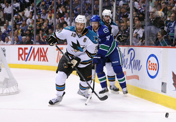 VANCOUVER, CANADA - MAY 24:  Joe Thornton #19 of the San Jose Sharks looks to play the puck out of the defensive zone against the San Jose Sharks Henrik Sedin #33 of the Vancouver Canucks hooks Thornto's stick in Game Five of the Western Conference Finals