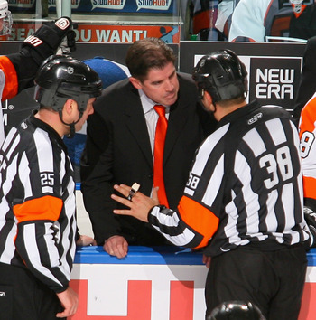 BUFFALO, NY - APRIL 20:  Head coach Peter Laviolette of the Philadelphia Flyers argues a penalty call with referee Francois St. Laurent #38 aginst the Buffalo Sabres  in Game Four of the Eastern Conference Quarterfinals during the 2011 NHL Stanley Cup Pla