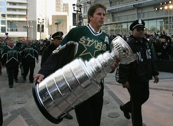 DALLAS - JANUARY 22:  Mike Modano #9 of the 1999 Dallas Stars Stanley Cup team walks with the Stanley Cup during the 1999 Dallas Stars Stanley Cup Reunion at the American Airlines Center on January 22, 2007 in Dallas, Texas.  (Photo by Bruce Bennett/Getty