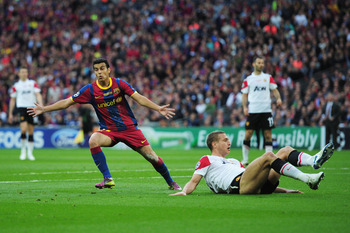 LONDON, ENGLAND - MAY 28:  Pedro of FC Barcelona (L) celebrates scoring the opening goal as Nemanja Vidic of Manchester United lies on the ground during the UEFA Champions League final between FC Barcelona and Manchester United FC at Wembley Stadium on Ma