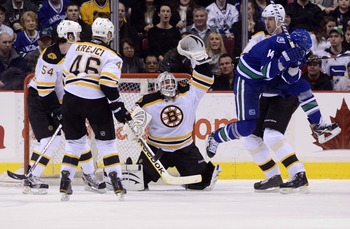 VANCOUVER, CANADA - FEBRUARY 26: Alexandre Burrows #14 of the Vancouver Canucks jumps out of the way of a shot as the puck sails over the head of goalie Tim Thomas #30 of the Boston Bruins during the third period in NHL action on February 26, 2011 at Roge
