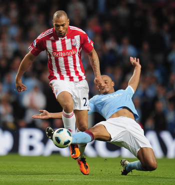 MANCHESTER, ENGLAND - MAY 17:  John Carew of Stoke City is tackled by Vincent Kompany of Manchester City during the Barclays Premier League match between Manchester City and Stoke City at City of Manchester Stadium on May 17, 2011 in Manchester, England.