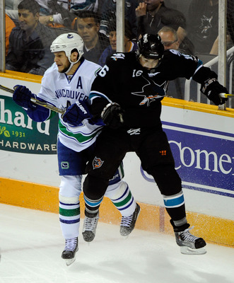 SAN JOSE, CA - MAY 20:  Kevin Bieksa #3 of the Vancouver Canucks and Devin Setoguchi #16 of the San Jose Sharks collide near the corner in Game Three of the Western Conference Finals during the 2011 Stanley Cup Playoffs at HP Pavilion on May 20, 2011 in S